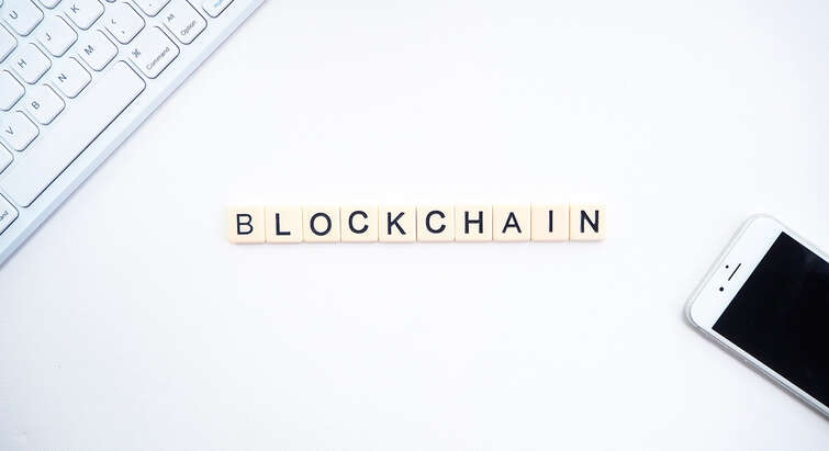 A keyboard, a phone, and scrabble letters spelling out the word blockchain